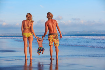 Happy family - father, mother, baby son hold hands, swim with fun, walk along sunset sea surf on black sand beach. Travel, active parents lifestyle, people activity on summer vacations with children.
