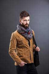 Portrait of bearded man with leather bag and stylish clothes looking at camera. Studio shot. Isolated