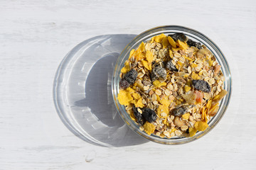 Home-made breakfast muesli with milk on white wooden background