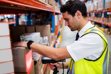 Warehouse manager with yellow coat scanning barcode on box