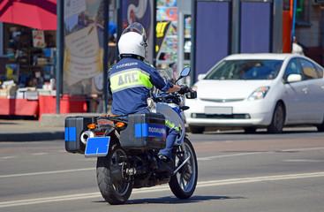 Патрульный инспектор дорожно-постовой службы (ДПС) едет на мотоцикле по улице