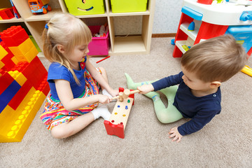 Two kids play with toy hammers and sticks in kindergarten