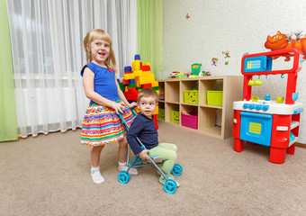 Little boy and girl play with toy stroller at home