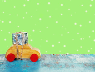 Wooden toy car carrying Christmas miniature gift on color background