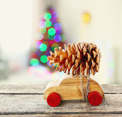Wooden toy car carrying Christmas pine on shiny lights background