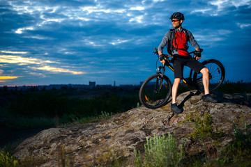 Cyclist Resting with Mountain Bike on the Rock at Sunset