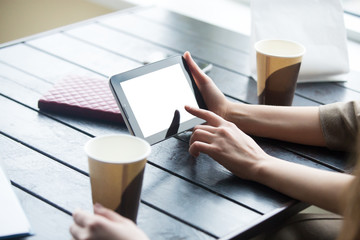 Women hands holding tablet with white blank screen in cafe. Clos