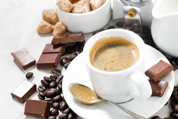 cup of espresso, coffee beans and sweets, closeup