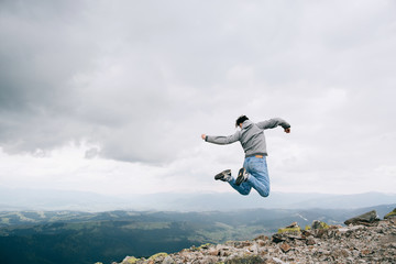 Young man Jumping Outdoors on rock in mountains sky