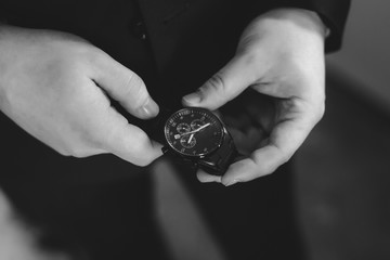 young man holding watch in his arms in black and white