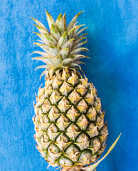 top of fresh pineapple on blue background