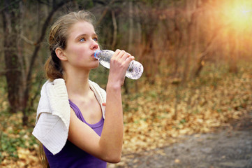 Sport girl runner is jogging on park stop and drink of bottle water path in park. Sport jogging .