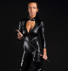 Woman with whip in latex dress