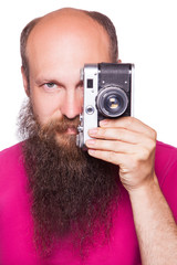 The portrait of bald bearded man photographer with pink t shirt holding classic camera. isolated on white background. studio shot.