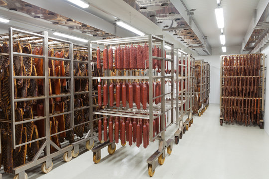 Fresh traditional sausages ready for drying in a smokehouse of a
