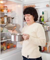 mature woman near   open refrigerator