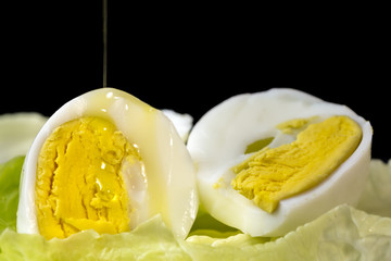 Trickle of  Extra Virgin olive oil falling over a hard boiled egg cut in half