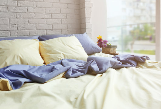 Unmade bed with crumpled blue bed linens on white brick wall background