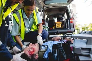 Ambulancemen healing injured man