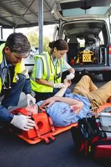 Ambulancemen healing injured man