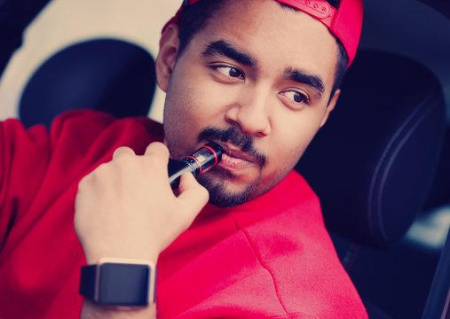 Young black boy smoking e-cig vaporizer in car