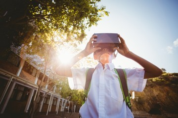 School boy in virtual reality glasses in campus