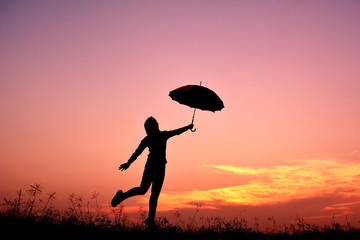 Silhouette women and umbrella in the sunset
