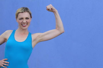Young smiling woman showing her bicep muscle with copy space