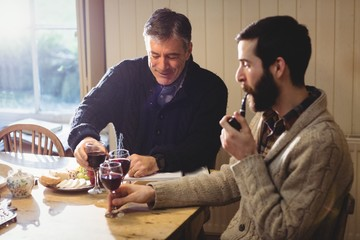 Mature and hipster man tasting red wine
