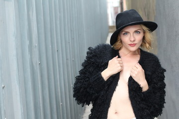Blonde sexy lady with glamour makeup and long hair posing wearing black fur jacket and a hat