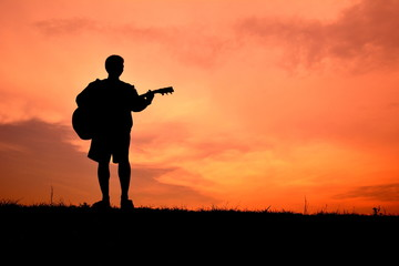 Silhouette man playin guitar in the sunset