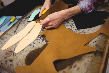 High angle view of cobbler cutting leather