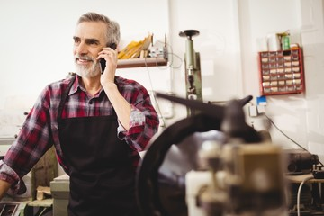 Cobbler calling with his mobile phone