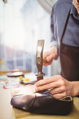 Close up of cobbler making a shoe with a hammer