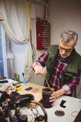 Cobbler mixing the wax
