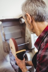 Rear view of cobbler using a sander machine