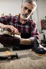 Portrait of cobbler polishing a shoe