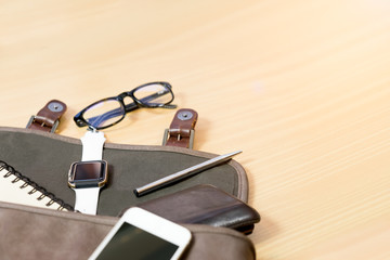 Outfit of traveler on wooden background: leather bag, smartwatch,smartphone, glasses, notebook and pen top view . retro style ,vintage tone