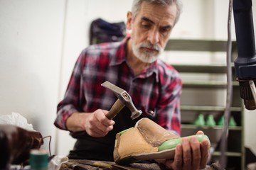 Low angle view of cobbler hammering on a shoe