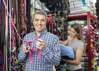 Customer Selecting Leash While Woman Holding Pet Bed