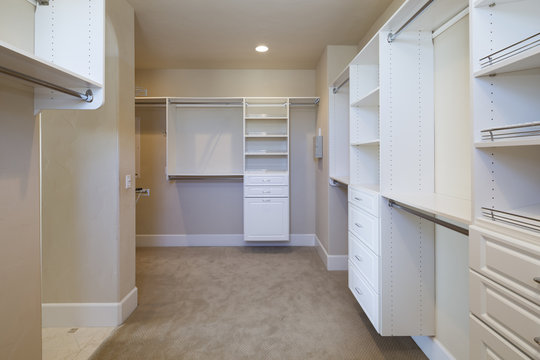 Large white walk-in closet with shelves.
