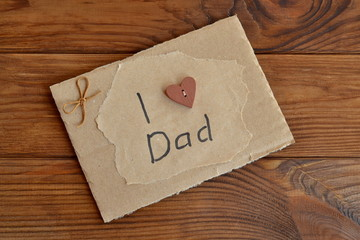 Homemade greeting card on wooden table. Card with text I love dad. Card is made by hand from cardboard box, wrapping paper, wooden button, cord. Children gift for father. Easy home present idea.