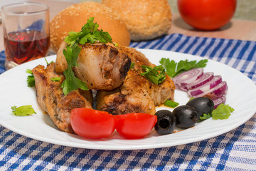 Delicious pork ribs grilled decorated with onion, black olives.