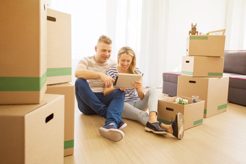 Couple surrounded with moving boxes looking at tablet
