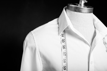 Shirt on manikin with white measurement tape