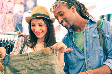 Interracial young couple searching clothing in street shop at the flea market - Concept of shopping and share  leisure time