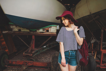 Funny Hipster Girl in old boat garage in island, Lots of boats.Trendy Casual Fashion Outfit in summer,spring. Toned Photo.