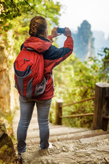Female tourist with red backpack and smartphone taking photo