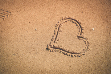 Love heart sign draw on sand background texture. joyful sunny outdoors