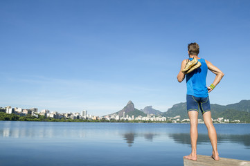 Brazilian athlete holding gold running shoes over his shoulder standing in front of the Rio de Janeiro, Brazil skyline at Lagoa Rodrigo de Freitas lagoon